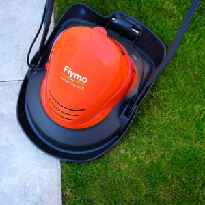 Flymo Turbo Lite 250 hovering over grass and tiles